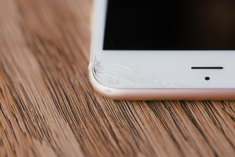 Macro view crack on the edge of the phone. Manicure. Wooden table in the cafe. stock photo