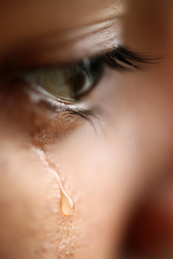 Macro view of an eye with tears. A macro view of an with tears showing sadness royalty free stock photography