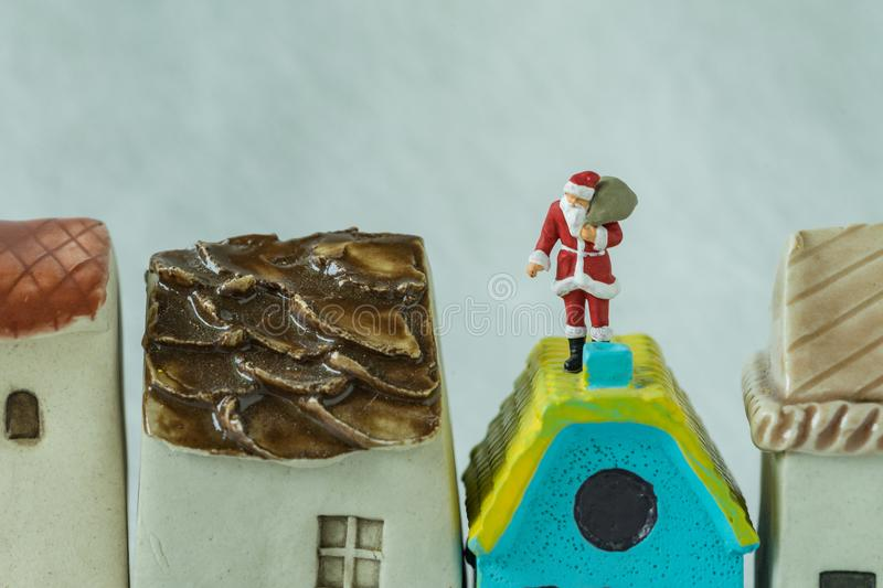 Macro view of miniature figure Santa claus standing on roof chimny as christmas celebration concept royalty free stock image
