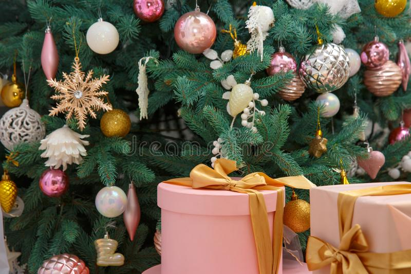 Macro view of pink present christmas box with gold ribbon. gift under the eve tree. With colorful toys stock image