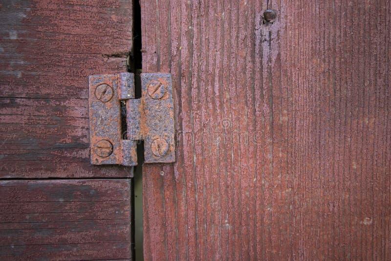 Macro view of rusty hinge on old wood door painted red royalty free stock photo