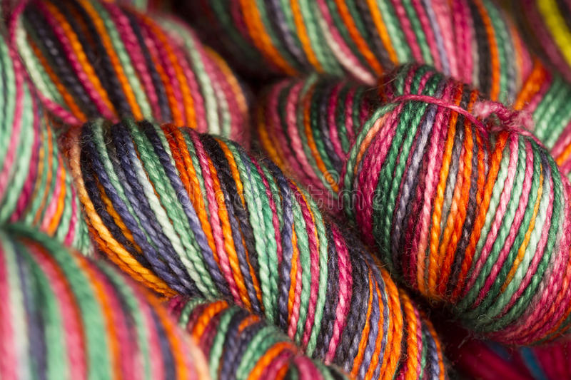 Macro View of several colorful Hanks of Yarn. Close up view of colorful hand dyed self striping yarn stock photography