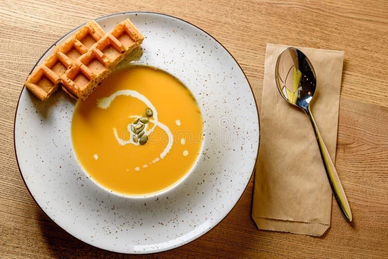 Macro vue de bol de soupe à potiron et à carotte, avec la gaufre belge fraîchement cuite au four image libre de droits