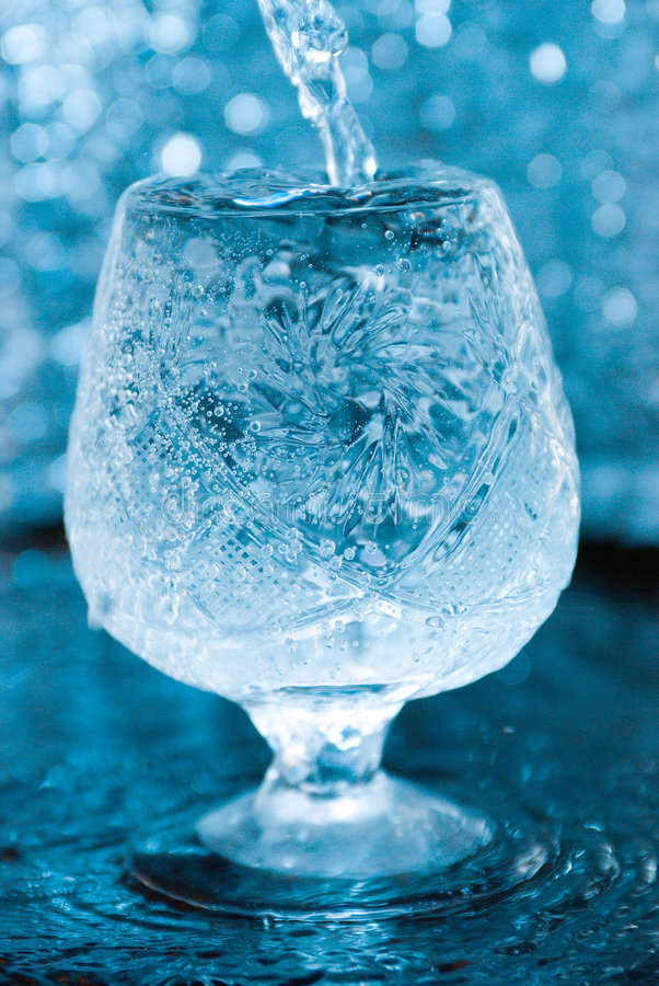 Macro of water poured into a glass of water royalty free stock image