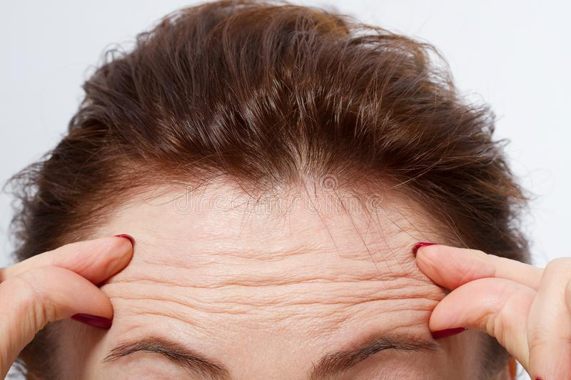 Macro Woman face with wrinkles on the forehead. Collagen and face injections concept. Menopause. Cropped image. Copy space and moc stock photography