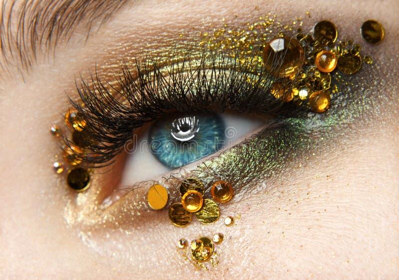 Macro y tema creativo del maquillaje del primer: ojo femenino hermoso con las sombras de oro y los diamantes amarillos, foto reto fotos de archivo libres de regalías