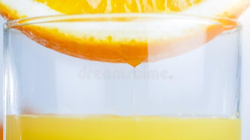 Macrobeeld van de sappige oranje helft bovenop glas met vers sap royalty-vrije stock fotografie