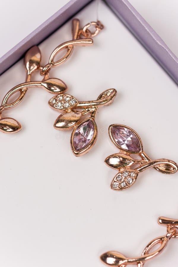 Macrobeeld van gouden oorringen met diamantstenen stock foto