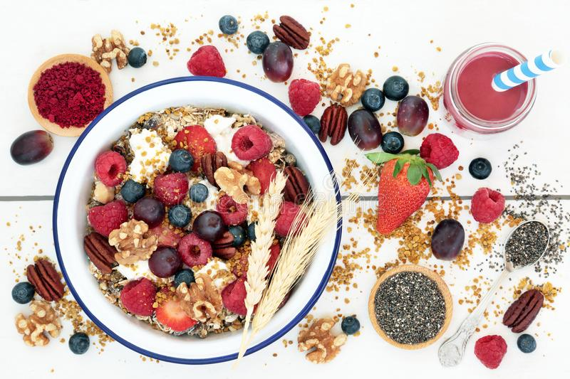 Macrobiotic Health Food for Breakfast. Concept with acai berry smoothie and powder, granola, pollen grain, berry fruit, chia seed and nuts with foods high in royalty free stock image