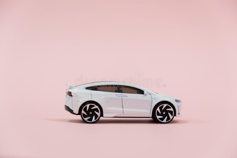 Macroclose-up van een witte stuk speelgoed auto op een roze achtergrond stock foto