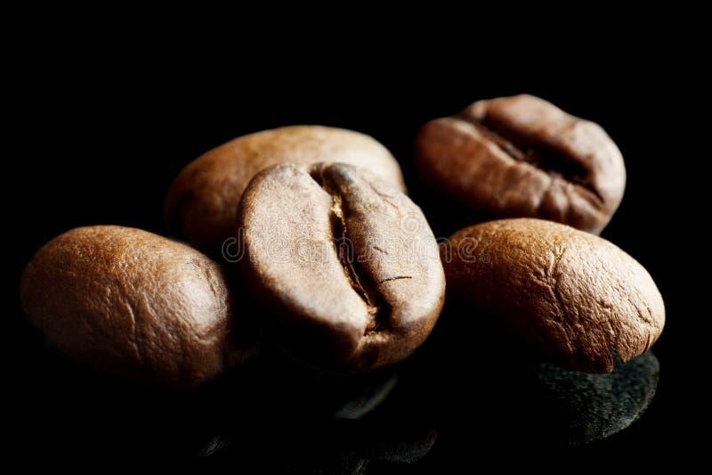 Macrodieclose-upschot van koffiebonen op zwarte worden geïsoleerd royalty-vrije stock afbeeldingen