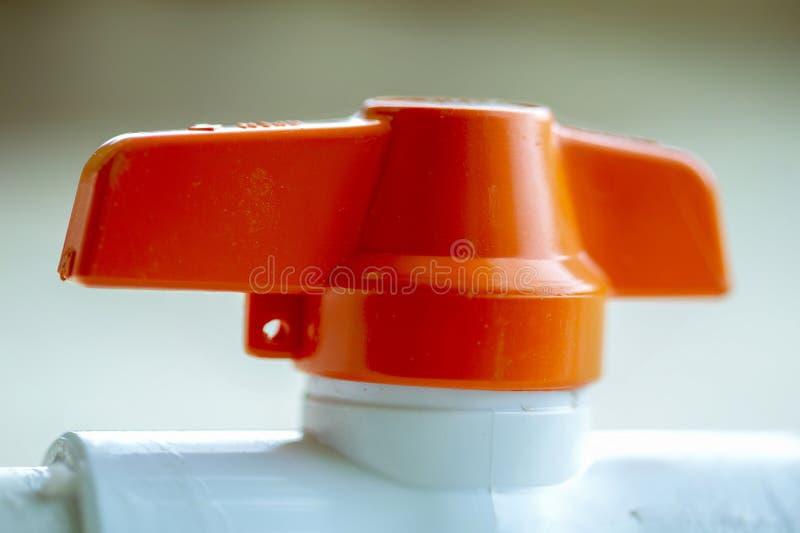 Macrofotografia di un rubinetto di chiusura arancio immagine stock libera da diritti