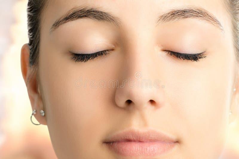 Macrogezichtsschot die van vrouw met gesloten ogen mediteren stock fotografie