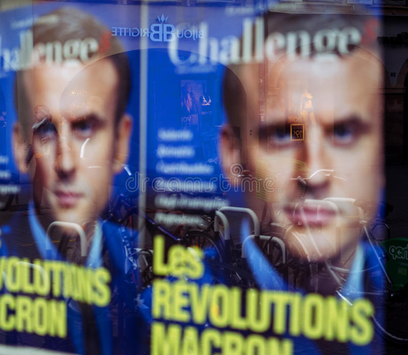 Macron revolution poster with city reflection. STRASBOURG, FRANCE - MAY 7, 2017: Macron revolution poster with pedestrians reflection in Press kiosk during the stock photography