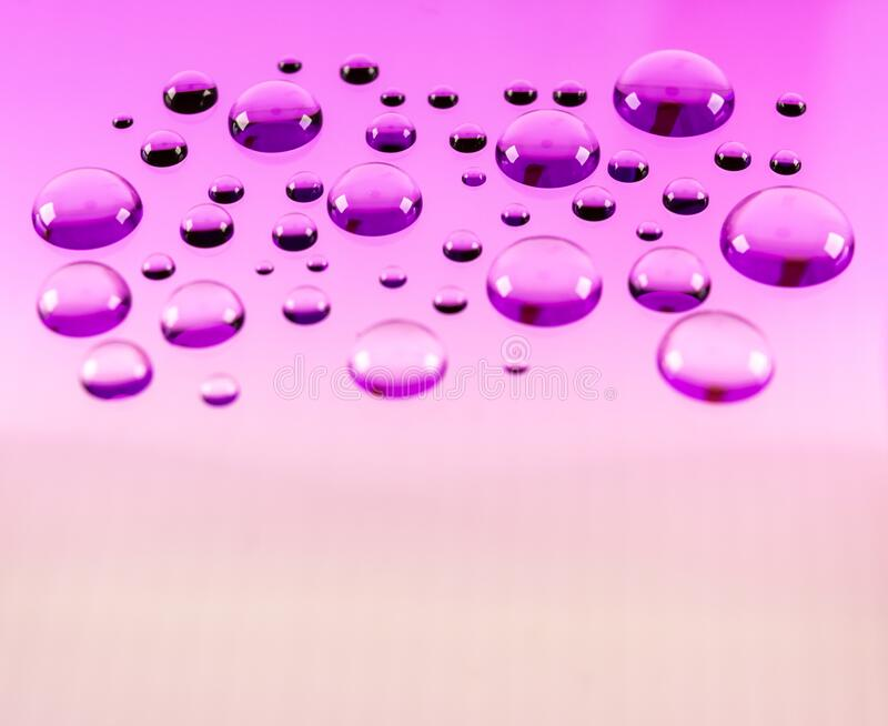 Macrophotography shot water droplet with purple background stock photography