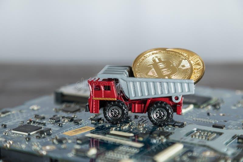 Macrostortplaatsvrachtwagen op Computermotherboard Het dumpen Gouden Bitcoin royalty-vrije stock afbeeldingen
