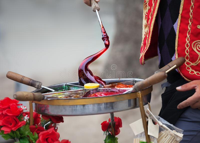 Macun, sweet Turkish toffee paste cooking on street. Macun - soft, sweet and colorful Turkish toffee paste in traditional container. Cooking street food in stock image