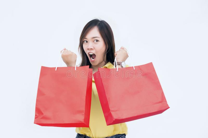 Mad action of asian lady hold shopping bag. Like win of sale festival on white background. lady in shopaholic concept royalty free stock images