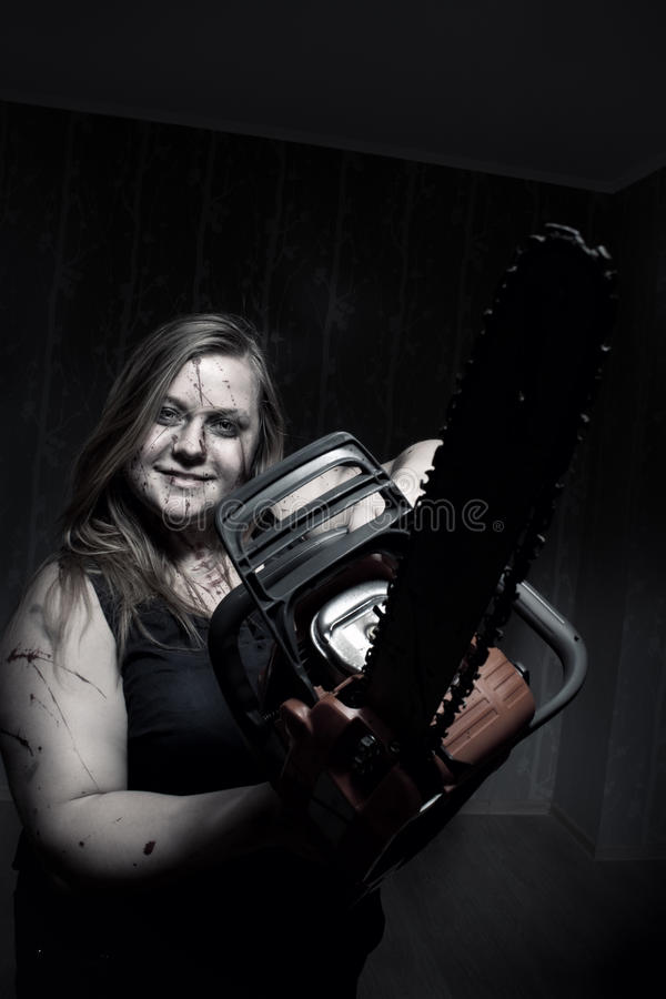 Mad girl with chainsaw royalty free stock images