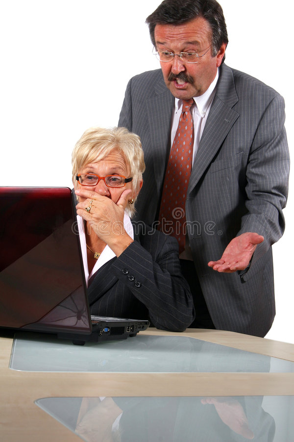 Mad Boss. A senior businesswoman in her fitifties is working on a laptopt in an office and seems to be shocked. Her boss behind her is angry. Isolated over white royalty free stock photography