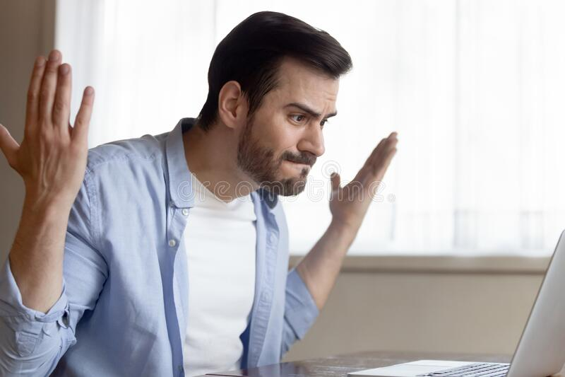 Mad Caucasian man having computer problems working on laptop. Angry Caucasian young male work on laptop at home get nervous having bad slow internet connection stock images