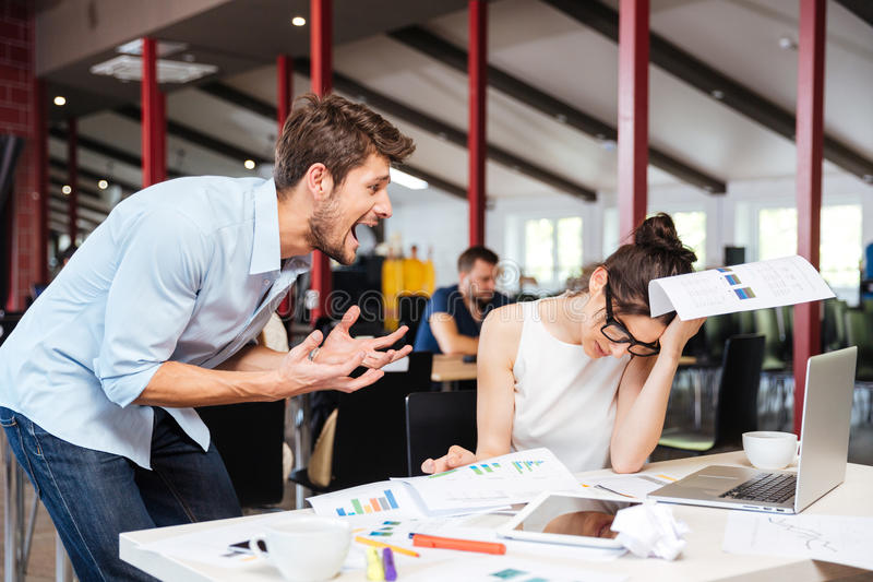 Mad crazy businessman arguing with sad stressed businesswoman in office stock photography