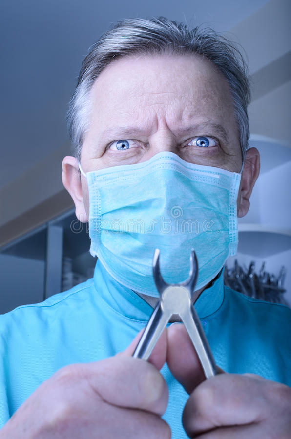 Mad dentist with pliers in his hands royalty free stock images