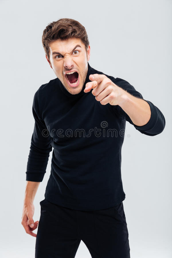 Mad furious young man pointing on you and shouting royalty free stock images