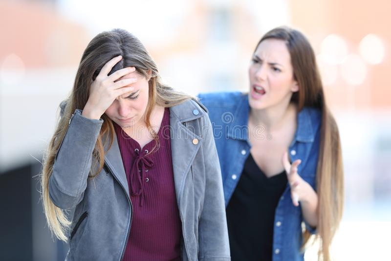 Mad girl scolding her concerned friend stock image