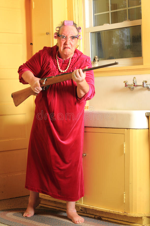 Mad Granny with Rifle. A mad senior gray haired granny lady wearing cat eye glasses, pearls and curlers in her hair in an old fashioned yellow kitchen standing stock image