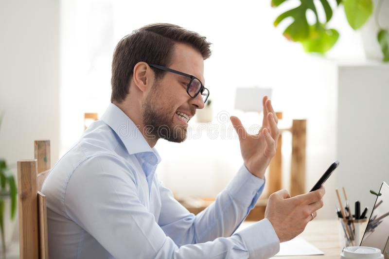 Mad male employee irritated by smartphone malfunction. Millennial employee irritated looking at smartphone having app problems, angry male worker holding royalty free stock images