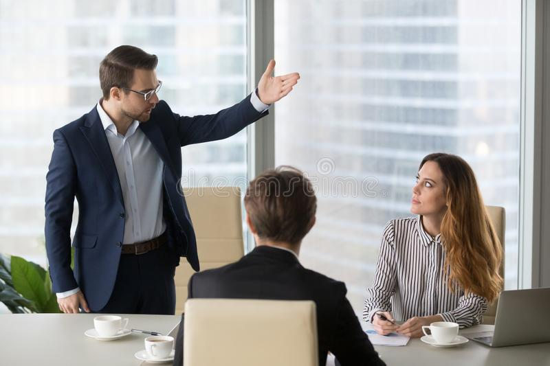Mad male worker asking female partner leave meeting royalty free stock image