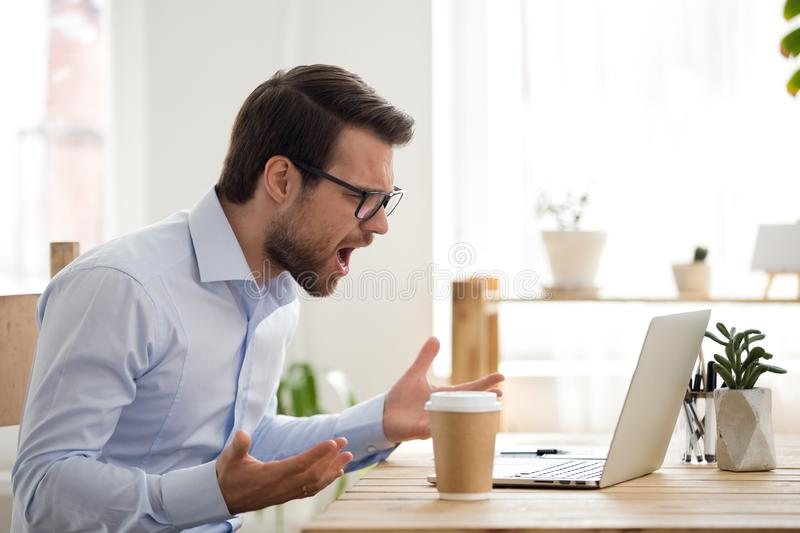 Furious male employee have laptop problems while working. Mad male worker lose temper scream loudly having computer problems or virus attack, furious man shout stock photo
