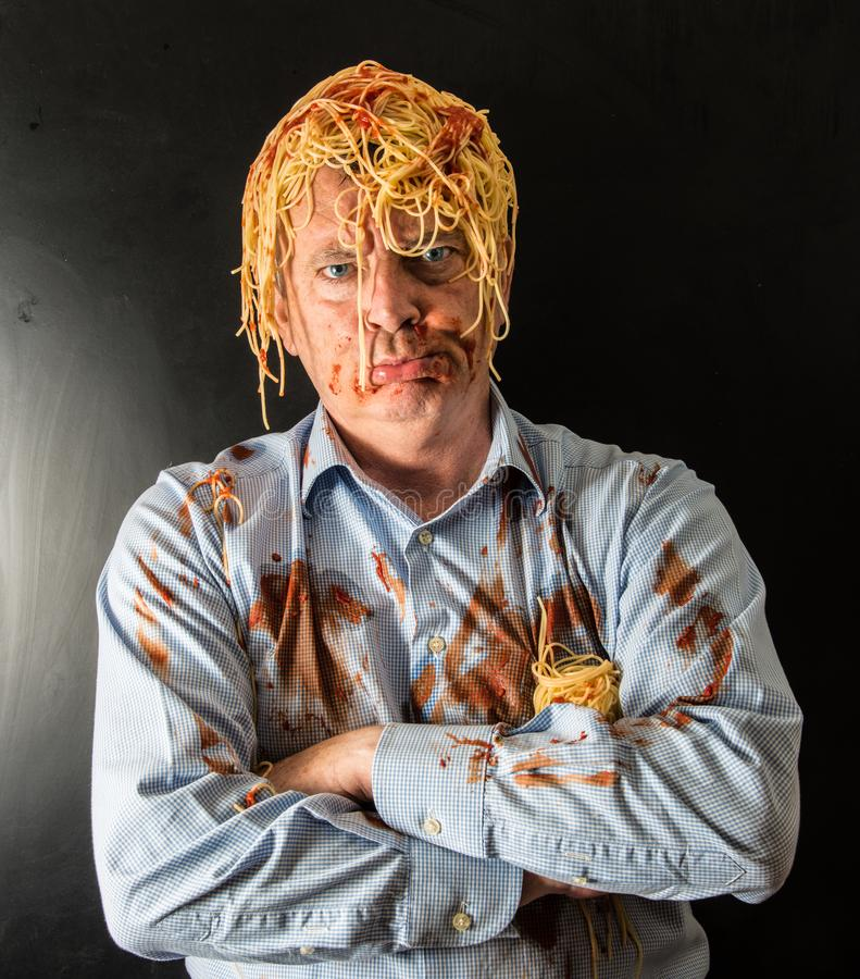 Man eating spaghetti with tomato sauce in head. Mad man eating spaghetti with tomato sauce in head stock image