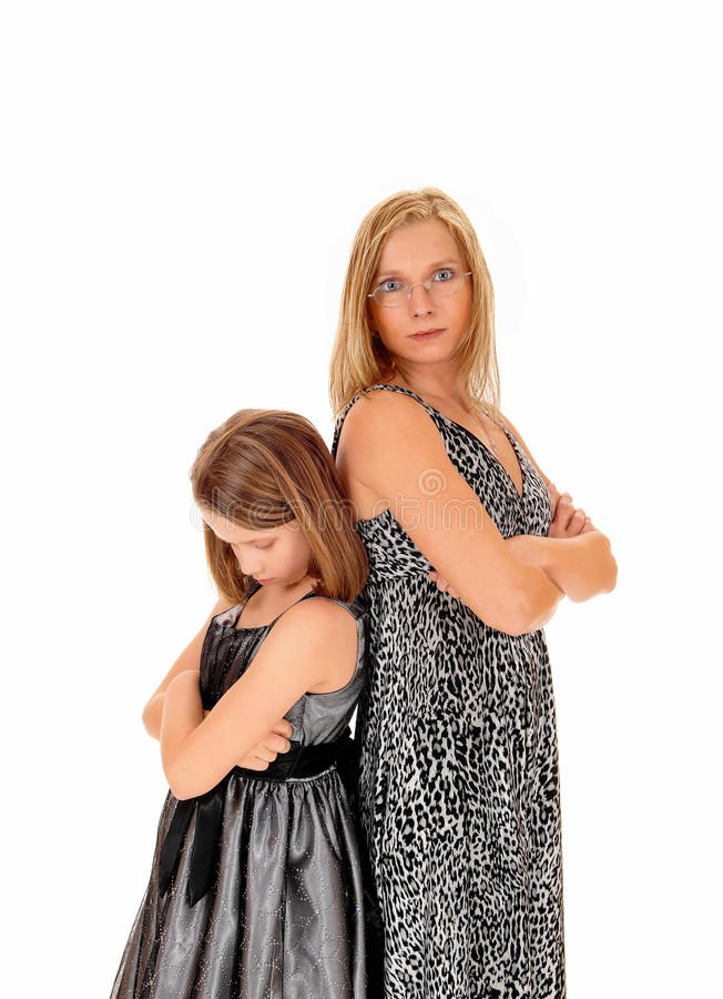 Mad mom and daughter. A mother and daughter standing back to back, isolated for white background, being mad to each other stock photography