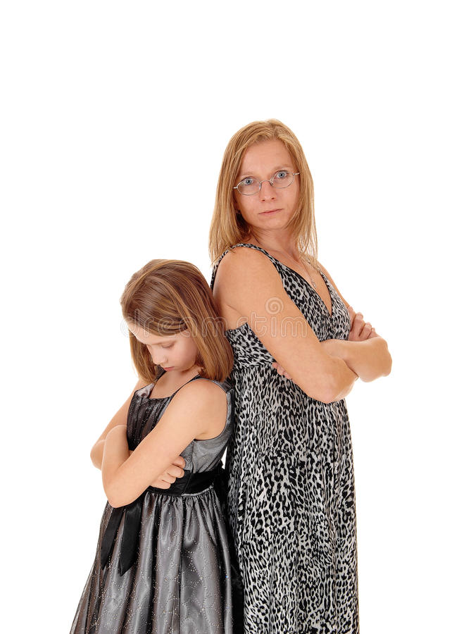 Mad mom and daughter. A mother and daughter standing back to back, isolated for white background, being mad to each other stock photo