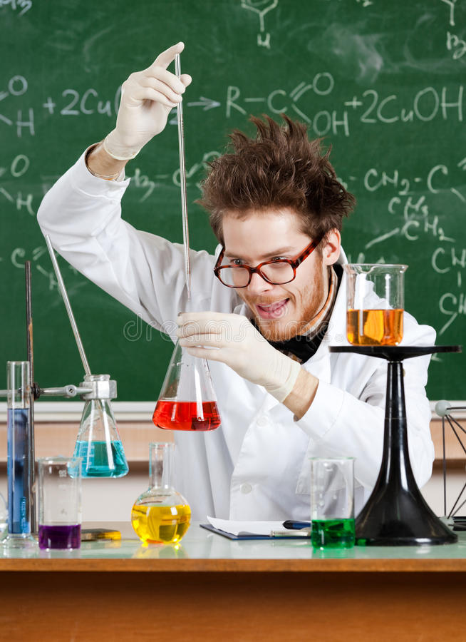 Mad professor adds something to the Erlenmeyer flask. With red water stock image
