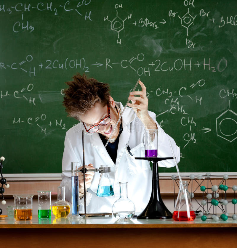 Mad professor holds an experiment. In his laboratory stock photos