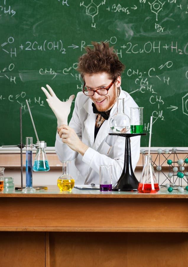 Mad professor puts a medical gloves on. Mad professor puts a medical rubber gloves on stock photography