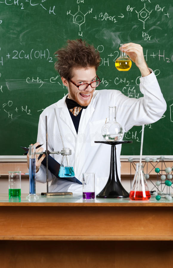 Mad professor shows flat-bottomed flask. In his laboratory stock photography