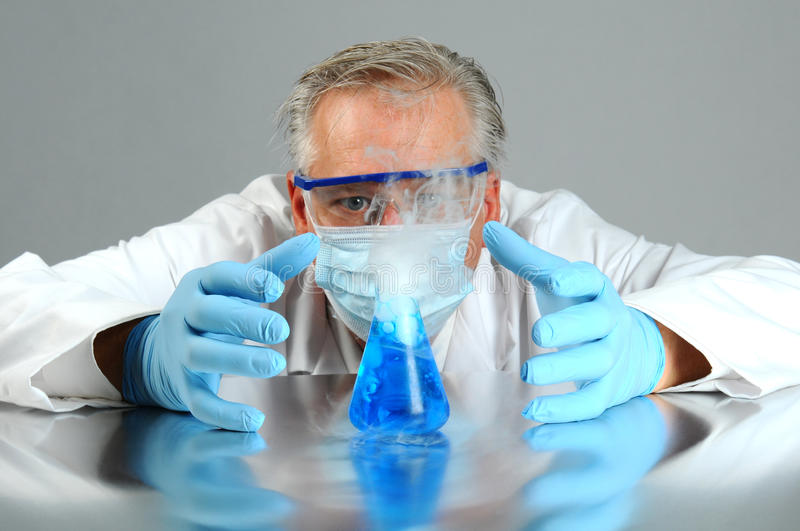 Mad scientist observes his experiment stock images