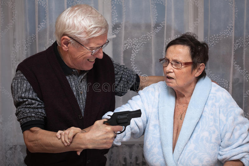 Mad senior with a gun stock image
