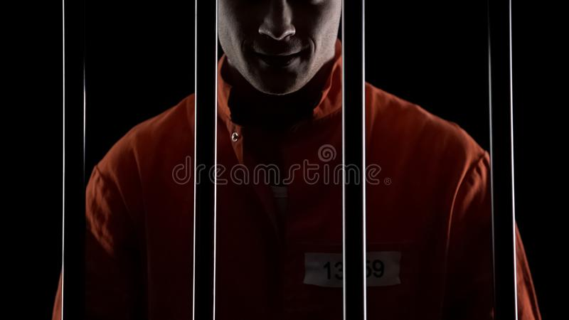 Mad serial killer standing behind prison bars and smirking, mental disorder. Stock photo royalty free stock photo