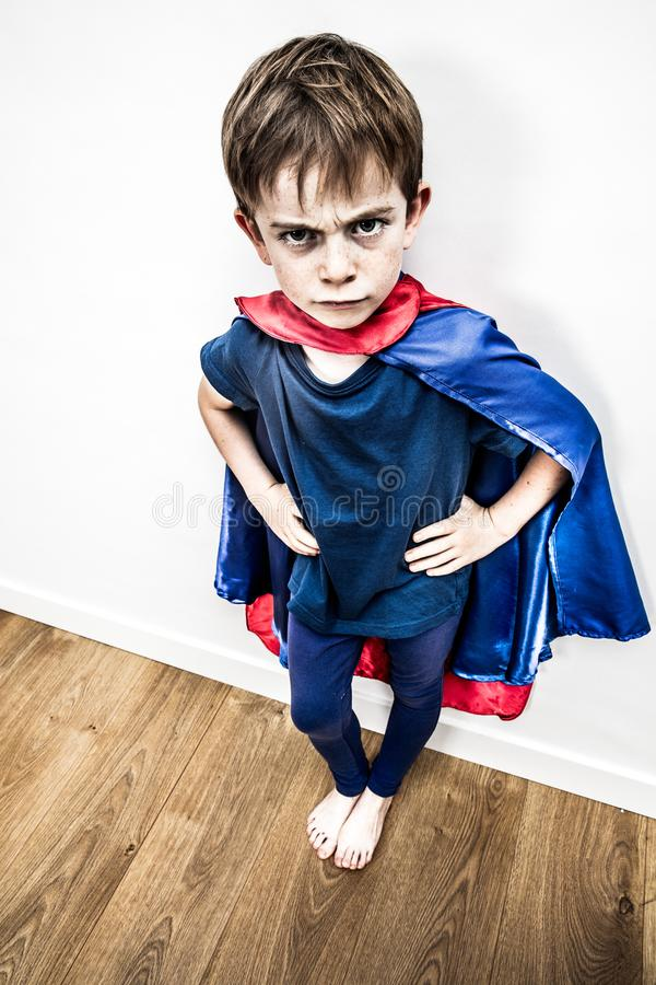 Mad superhero boy being outraged by denigrating education, contrast effect. Mad superhero boy with hands on hips being outraged, irritated, offended by a royalty free stock images