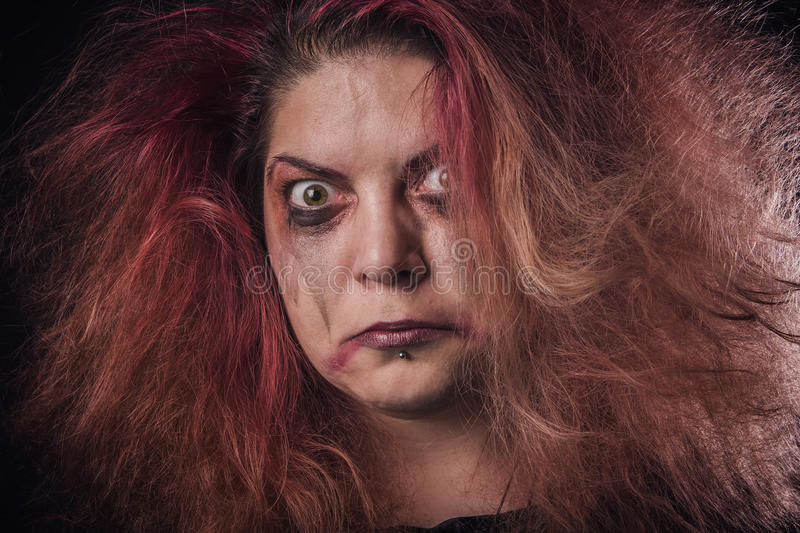 Mad woman looking scary. Deranged girl with a dangerous face stock photo
