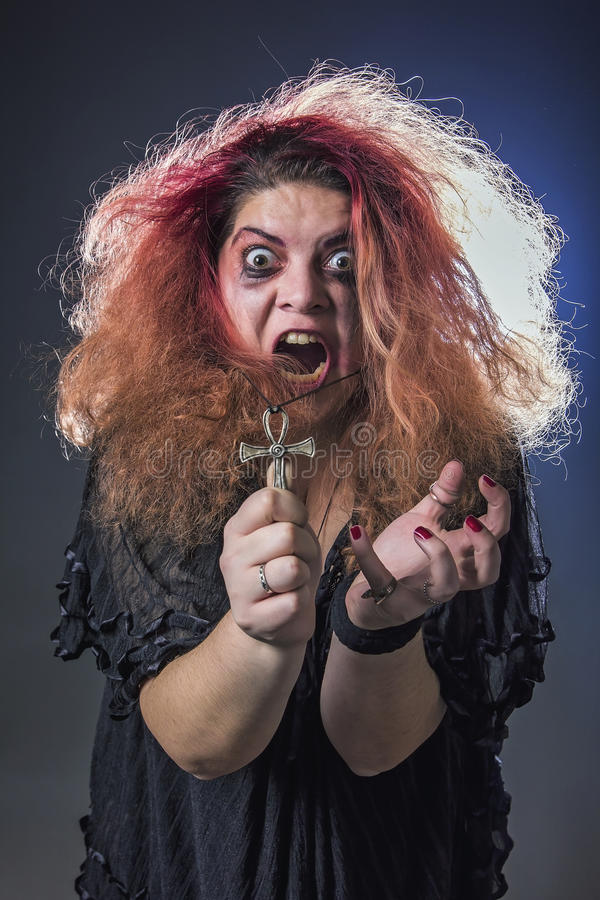 Mad woman screaming. Deranged young woman holding an ankh necklace and screaming in terror royalty free stock photos