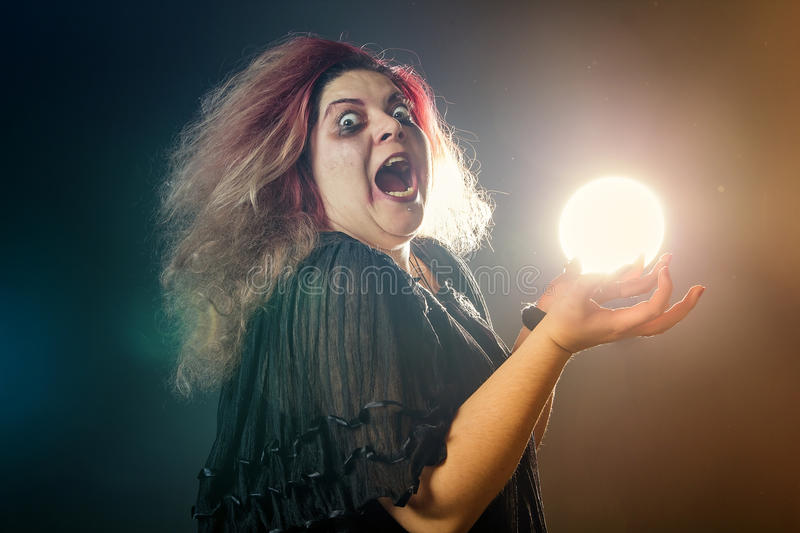 Mad woman screaming. Deranged young woman holding a ball of light stock photo