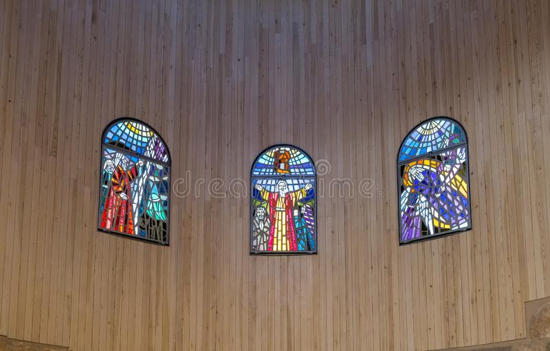 Stained glass windows hang on the wall in the prayer hall of Memorial Church of Moses on Mount Nebo near the city of Madaba in Jor royalty free stock photo