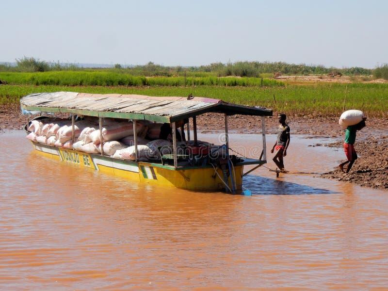 Madagascar ładunku łódź na rzece, chłopiec rozładowywa torby obraz royalty free