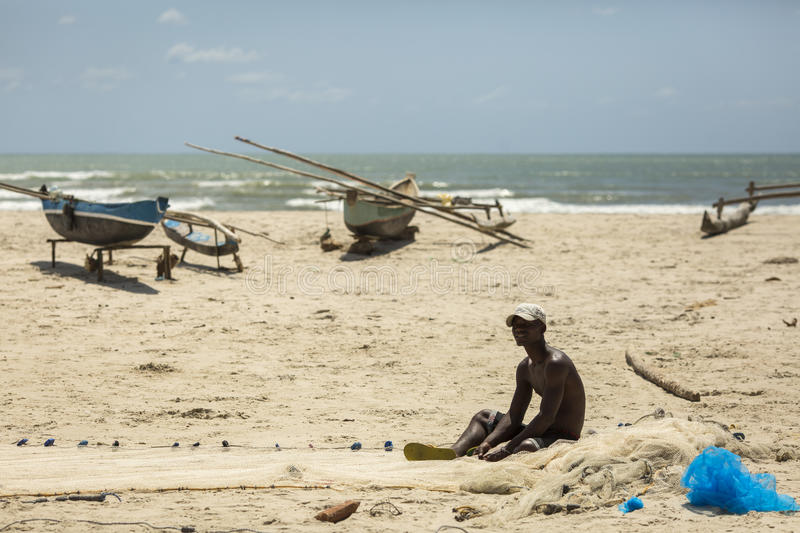 MADAGASCAR, MORONDAVA - OCTOBER 5, 2016: Local resident fisherman preparing for fish on the beach in Morondava. Madagascar, Moron stock photos